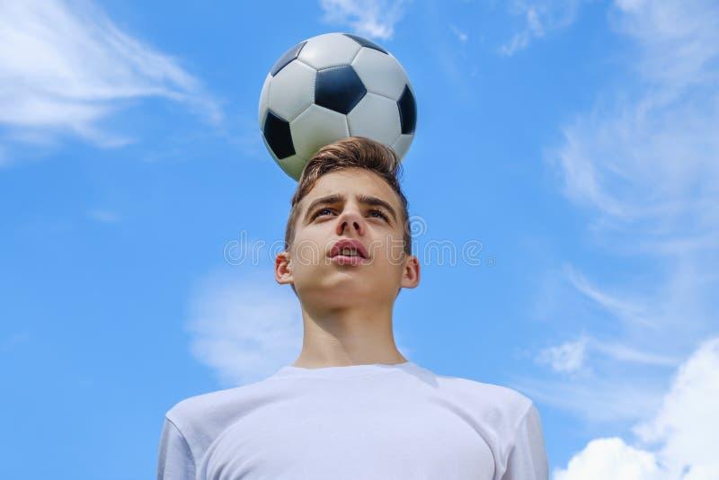 Tiener met een voetbalbal op a van blauwe hemel stock foto's