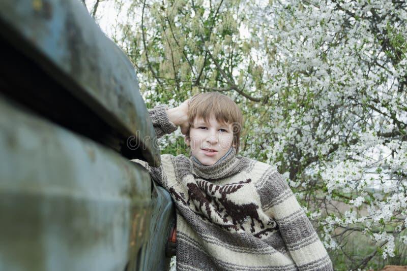 Tiener met gebreide wollige rendier warme sweater die oud vrachtwagenlichaam leunen in openlucht dichtbij bloeiende fruitboom stock foto's