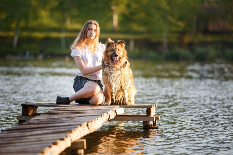 Tiener met haar hondzitting in park stock foto's