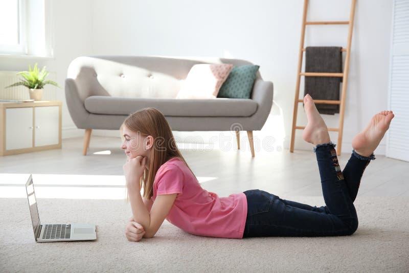 Tiener met laptop die op comfortabel tapijt liggen stock fotografie