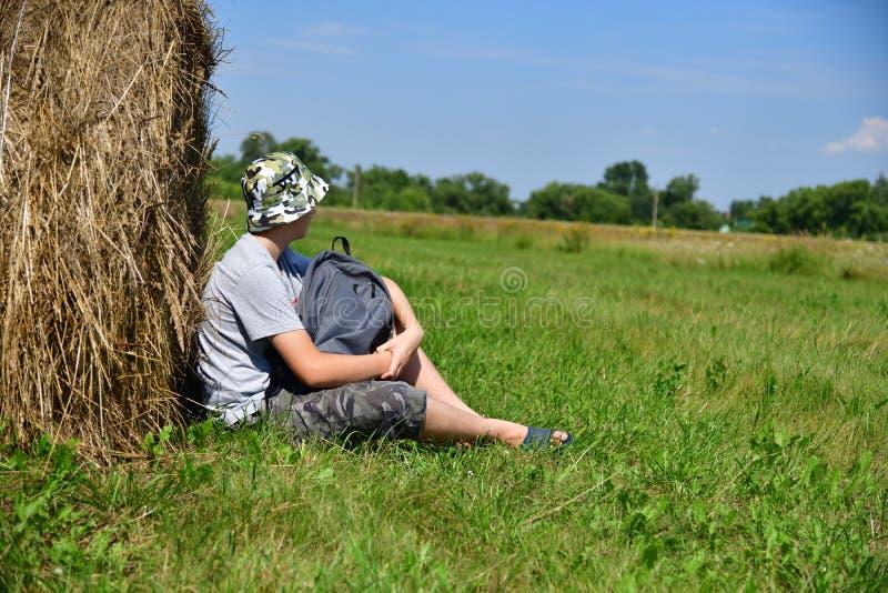 tiener met rugzakzitting naast stapel van stro stock afbeeldingen