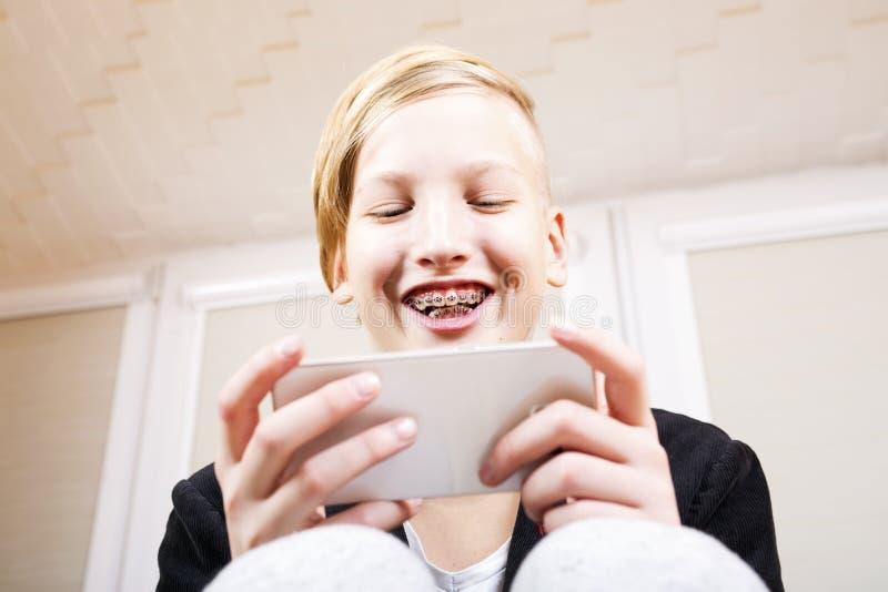 Tiener met steunen op zijn tanden met telefoon stock afbeeldingen