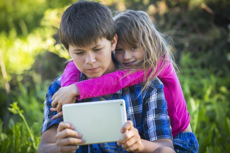 Tiener met zijn jongere zusterzitting in openlucht en gebruikend de tablet Famale royalty-vrije stock afbeeldingen