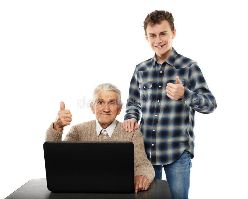 Tiener met zijn opa bij laptop stock foto