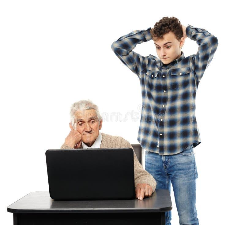 Tiener met zijn opa bij laptop royalty-vrije stock foto's