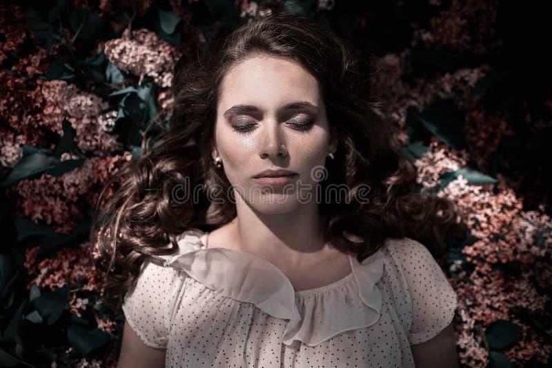 Tiener mooi meisje die op lilac bloemenachtergrond liggen Dichte omhooggaand van het portret royalty-vrije stock afbeelding