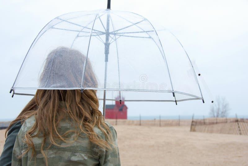 Tiener onder paraplu op strand stock foto