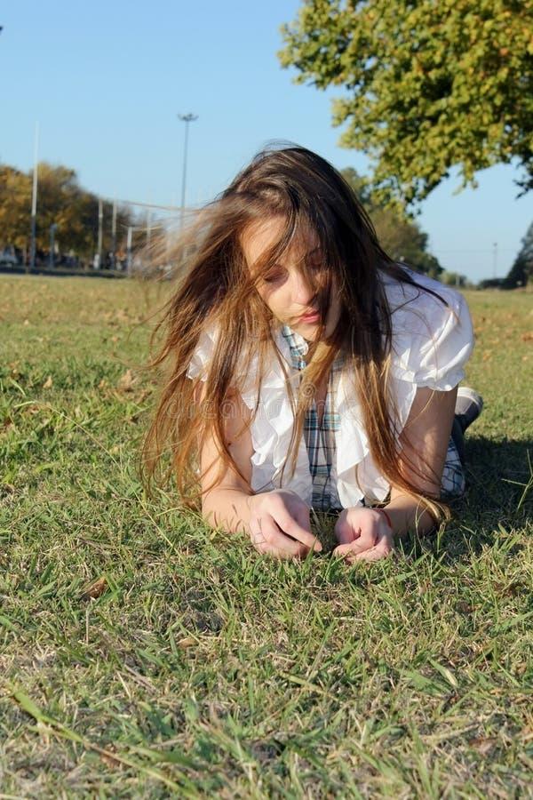 Tiener op het gras in het park royalty-vrije stock afbeelding