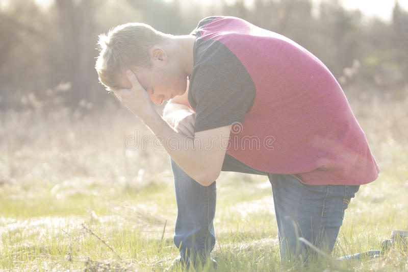 Tiener op knie en het bidden op open gebied stock fotografie