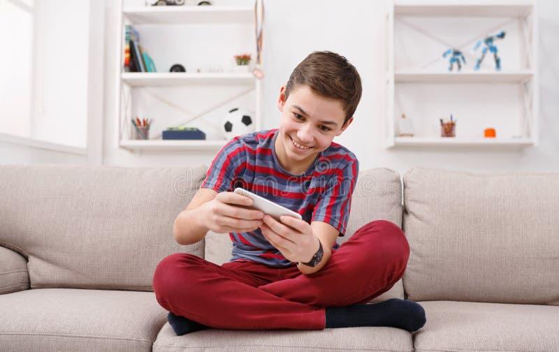 Tiener speelspelen op smartphone stock afbeeldingen