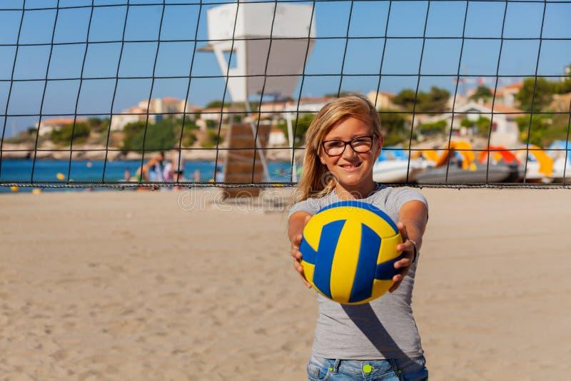 Tiener speelvolleyball op het strand stock afbeelding