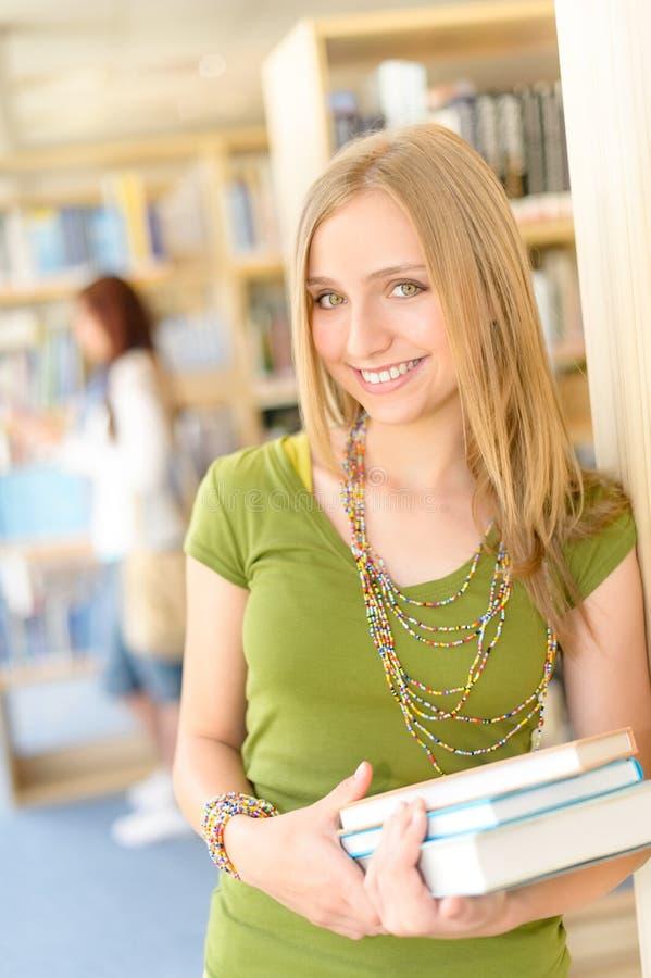Tiener student met boek bij middelbare schoolbibliotheek stock afbeeldingen
