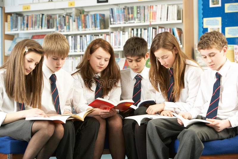 Tiener Studenten in de Boeken van de Lezing van de Bibliotheek royalty-vrije stock foto's