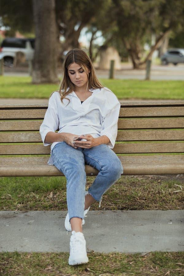 Tiener Texting in het Park stock afbeelding