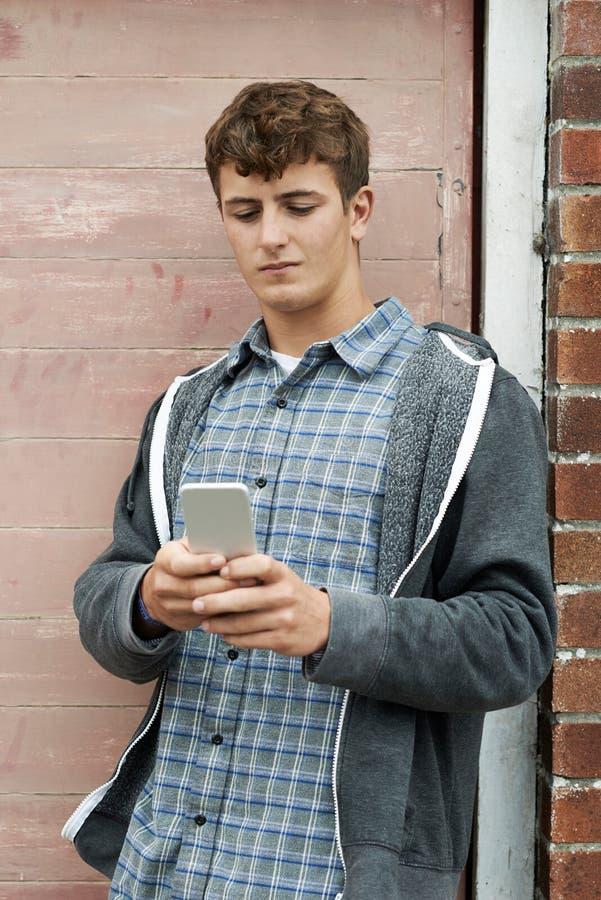 Tiener Texting op Mobiele Telefoon in het Stedelijke Plaatsen stock fotografie