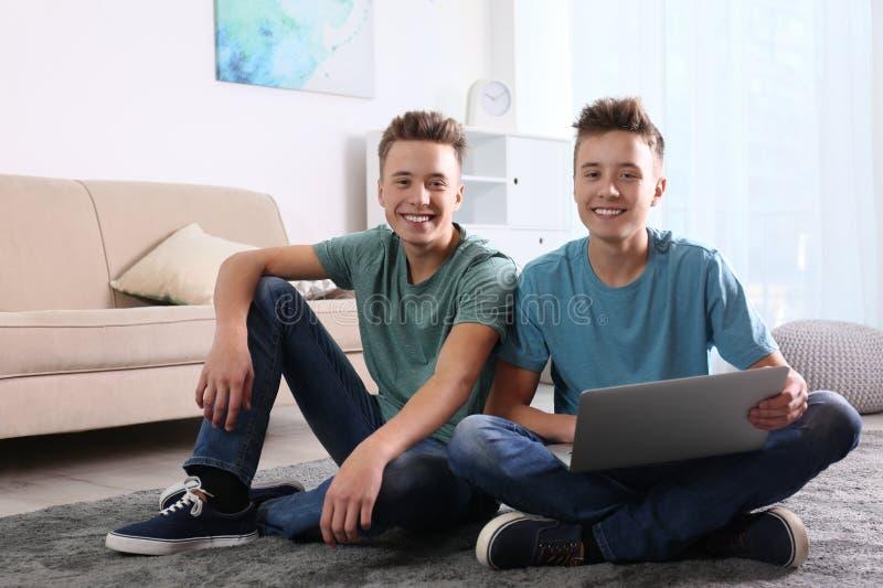 Tiener tweelingbroers die laptop samen met behulp van stock foto's