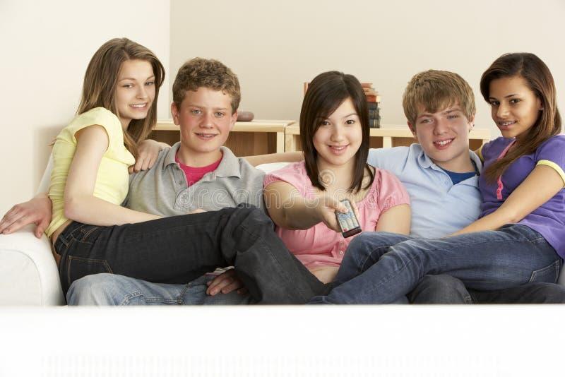 Tiener Vrienden die op Televisie thuis letten stock fotografie