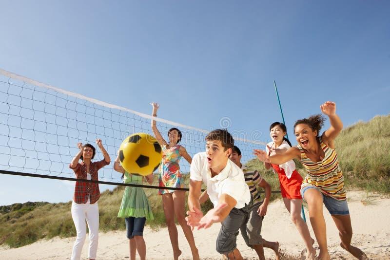 Tiener Vrienden die Volleyball op Strand spelen stock foto's