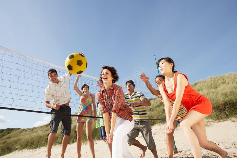 Tiener Vrienden die Volleyball op Strand spelen royalty-vrije stock foto's