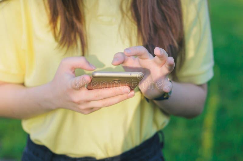 Tiener wat betreft het scherm Vrouw die een mobiele telefoon in handen houden stock afbeeldingen