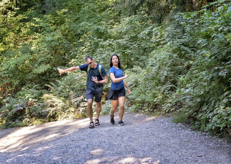 Tieneramerasian-meisje en haar Kaukasische vader die een steile heuvel, Snoqualmie-Park, Staat beklimmen van Washington royalty-vrije stock foto's