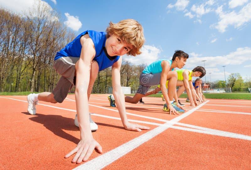 Tieneratleten die voorbereidingen treffen beginnen te lopen stock foto