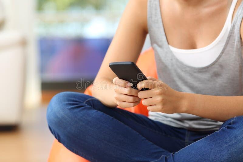 Tienerhanden die een slimme telefoon thuis met behulp van royalty-vrije stock afbeeldingen