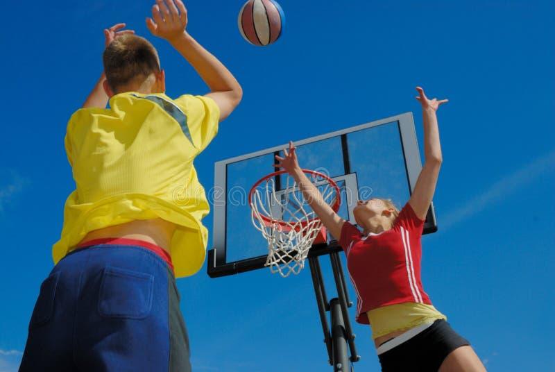 Tienerjaren die basketbal spelen stock fotografie