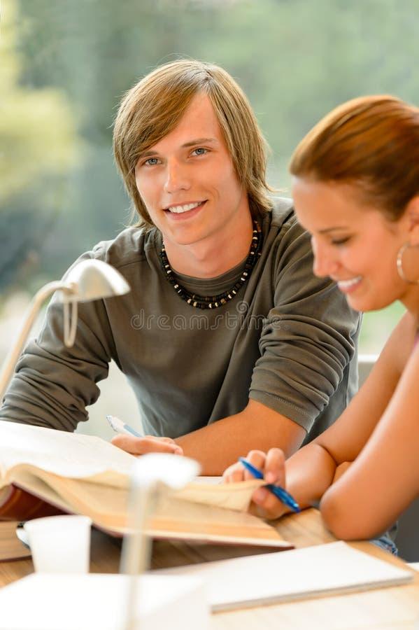 Tienerjaren die boek lezen dat in middelbare schoolbibliotheek bestudeert royalty-vrije stock fotografie