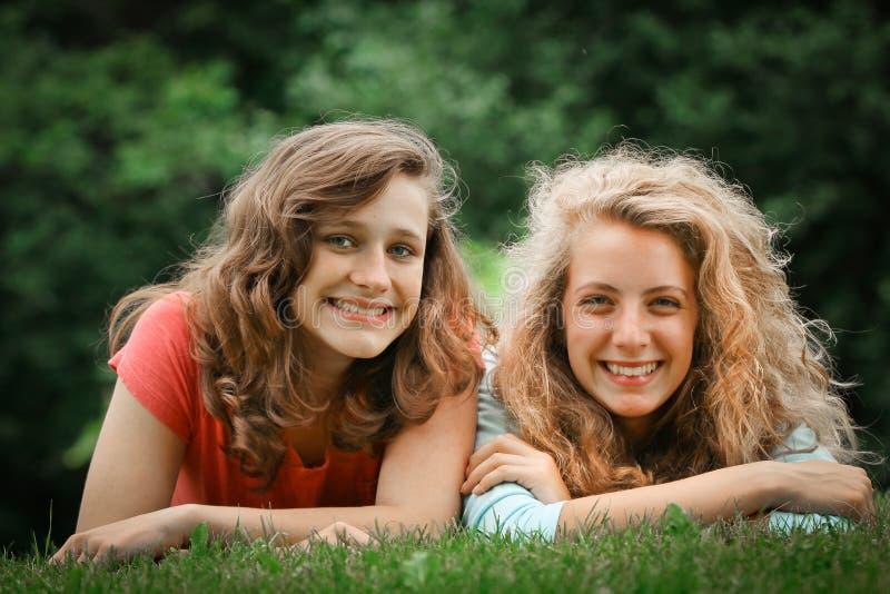 Tienerjaren die in een gras liggen stock afbeelding