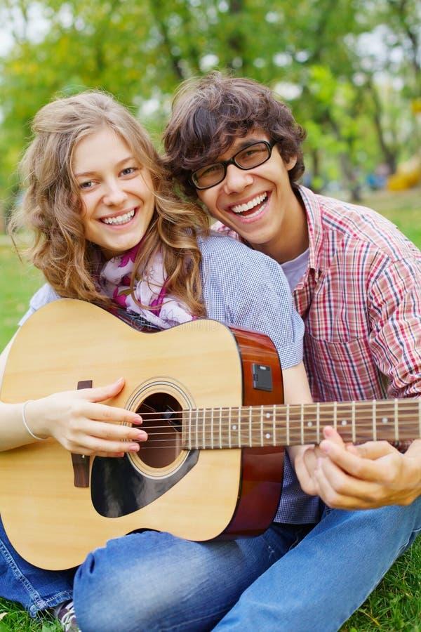 Tienerjaren die pret met gitaar in park hebben royalty-vrije stock afbeelding