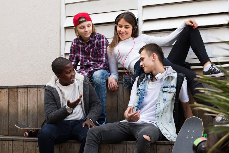 Tienerjaren die in zonnige dag spreken royalty-vrije stock afbeeldingen