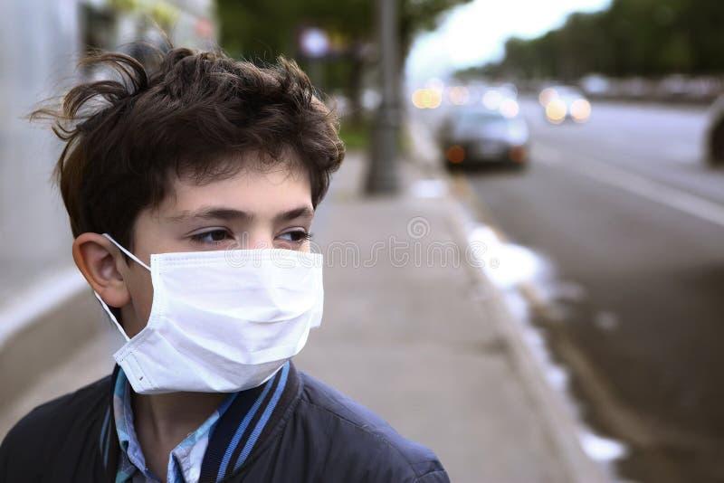 Tienerjongen in beschermingsmasker op de wegstad stock fotografie