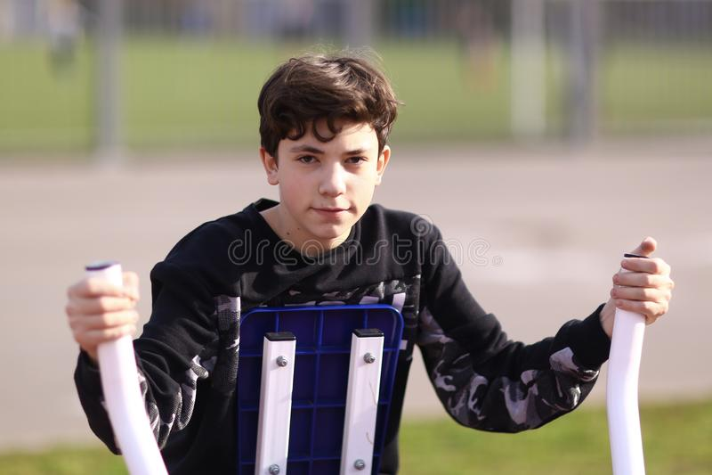Tienerjongen de bicepsen van het opleidingswapen in openluchtgymnastiek in de foto van het stadspark dicht omhoog stock foto's