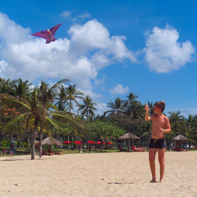 Tienerjongen die een vlieger op tropisch strand vliegen royalty-vrije stock foto