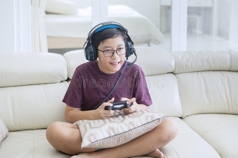 Tienerjongen die hoofdtelefoons dragen om videospelletjes te spelen royalty-vrije stock fotografie