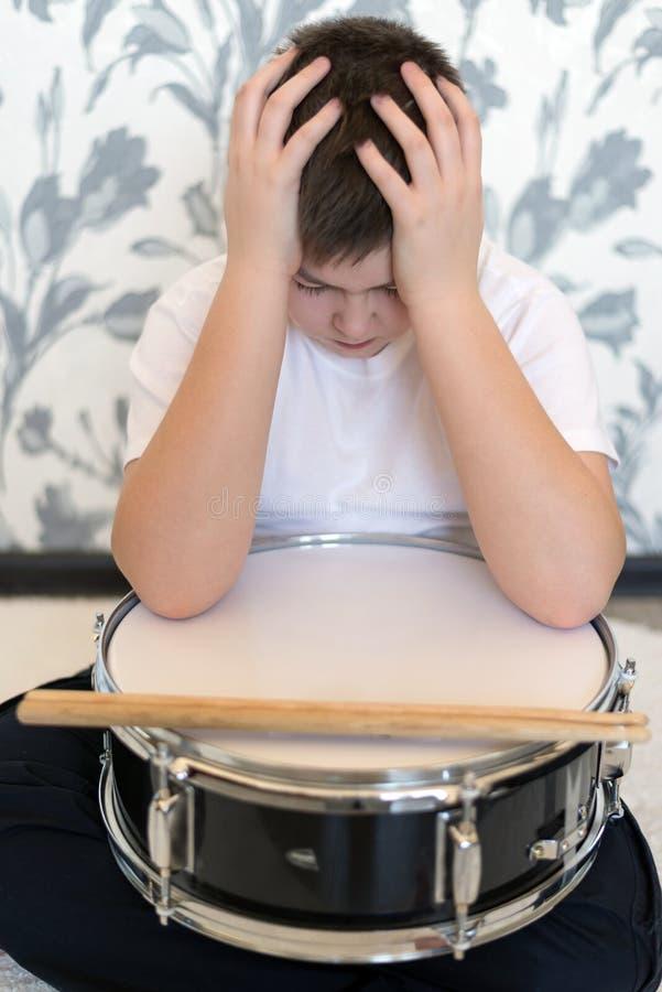 Tienerjongen die met trommel zijn hoofd houden stock fotografie