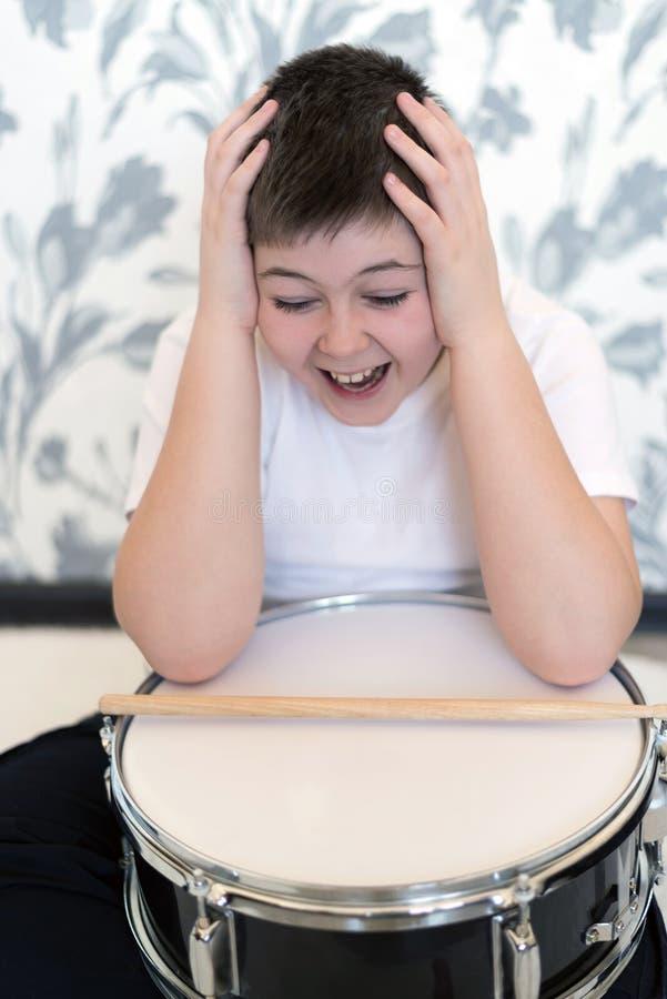 Tienerjongen die met trommel zijn hoofd houden stock afbeelding