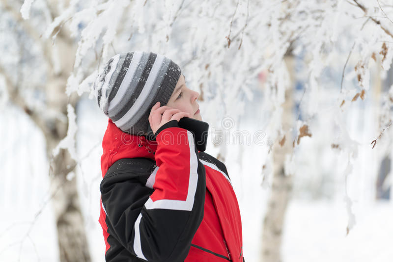 Tienerjongen die op de telefoon in de winterpark spreken stock afbeelding