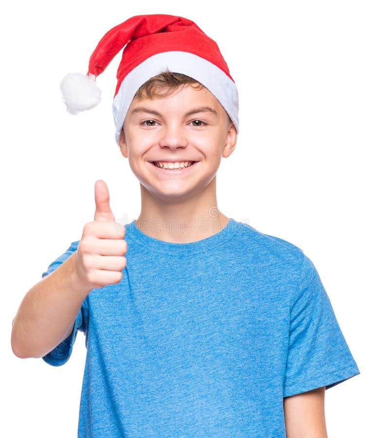 Tienerjongen die Santa Claus-hoed dragen stock foto