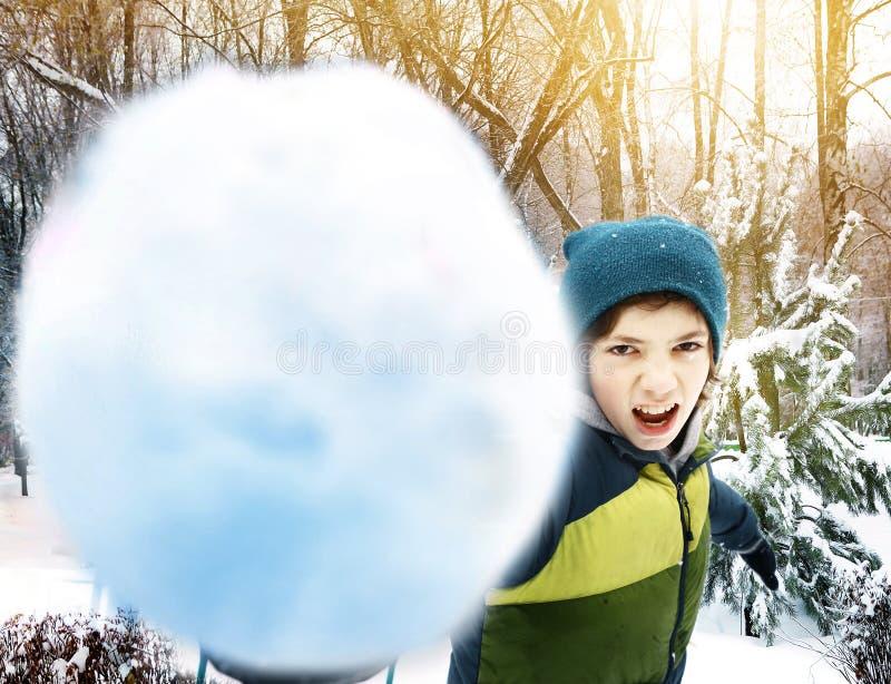 Tienerjongen die sneeuwbal werpen openlucht stock afbeelding