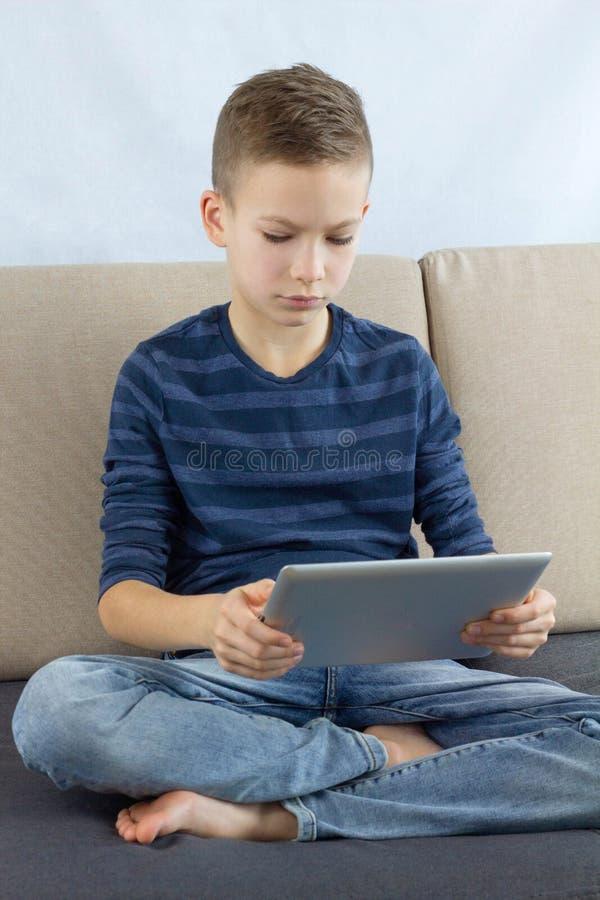 Tienerjongen die touchscreen tablet gebruiken Jong jongens speelspel of thuis het controleren van sociale media op tablet Het onl stock foto