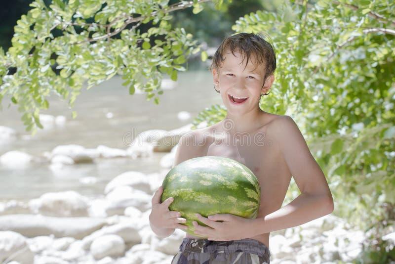 Tienerjongen die verse groene watermeloen in handen houden stock foto