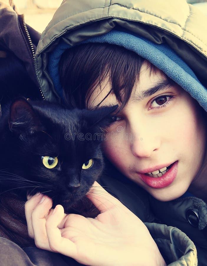 Tienerjongen en zwarte kat royalty-vrije stock fotografie