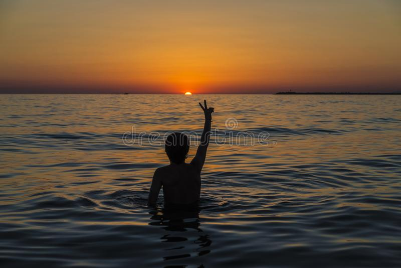 Tienerjongen het baden in het overzees bij zonsondergang in Sicilië royalty-vrije stock foto's