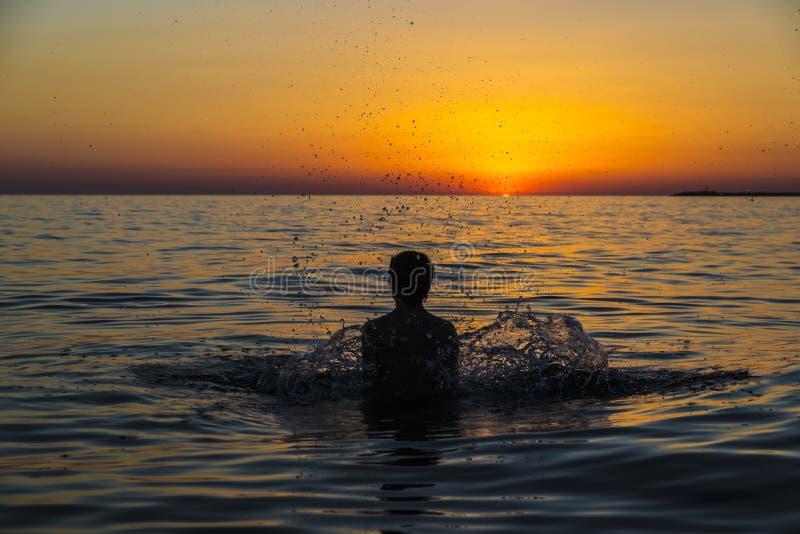 Tienerjongen het baden in het overzees bij zonsondergang in Sicilië stock foto's