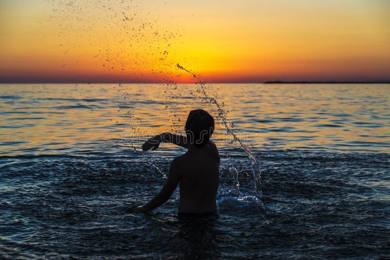 Tienerjongen het baden in het overzees bij zonsondergang in Sicilië royalty-vrije stock fotografie