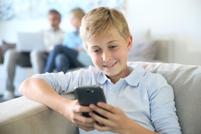 Tienerjongen het spelen met smartphone thuis stock foto's