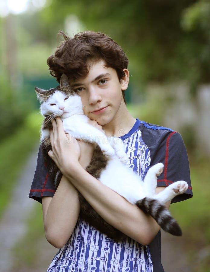 Tienerjongen met kat knuffelknuffel stock foto's