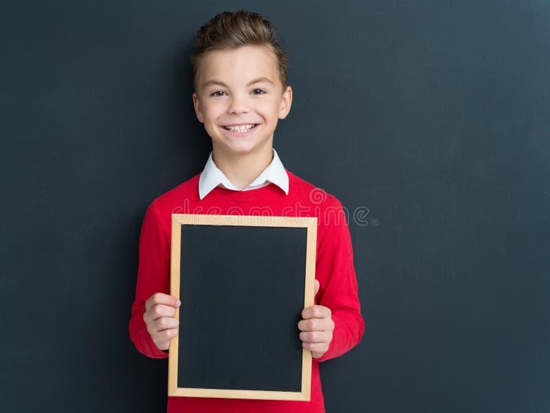 Tienerjongen met klein bord stock afbeelding